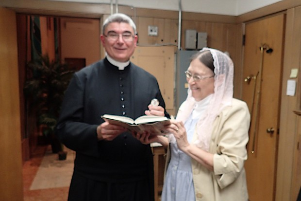 PLMC Board member Cynthia Medvitz presenting Fr. Cizik with a copy of the Oxford Dictionary of Saints