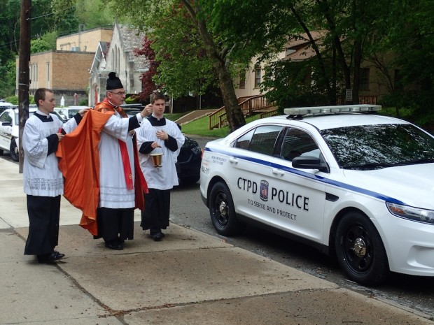 Fr. Cizik blesses the police vehicles